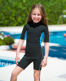 Happy little girl in a wetsuit. Near the pool in the summer Royalty Free Stock Images