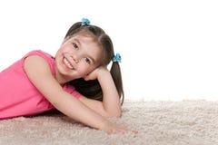 Happy little girl on the white carpet Stock Photo