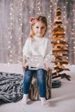 Happy little girl in a white sweater and blue jeans posing near christmas tree Stock Image