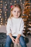 Happy little girl in a white sweater and blue jeans posing near christmas tree Royalty Free Stock Image