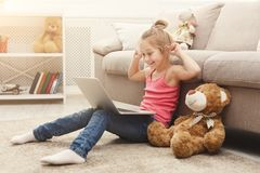 Beautiful female child playing online game on laptop stock photo