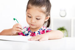 Happy little girl writing  in  notebook Stock Images