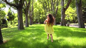 Happy little girl with yellow dress running barefoot on green grass in the park stock video footage