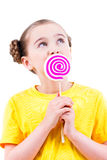 Happy little girl in yellow t-shirt eating colored candy. Royalty Free Stock Image