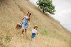 Mother and daughter walking on hill. Happy little girl and young women with suitcase holding hands and walking on grassy hill Stock Images