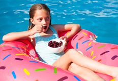 Girl sitting on a colorful inflatable donut with cherries Royalty Free Stock Photography