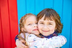 Happy little girlfriends embrace. Outdoor. Colourful background Stock Photos