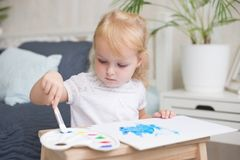Happy little girlpainting with gouache and watercolor paints on the easel indoors. royalty free stock image