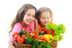Happy little girls with basket of vegetables Stock Images