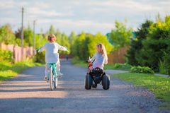 Happy little girls biking outdoors at the park Royalty Free Stock Image