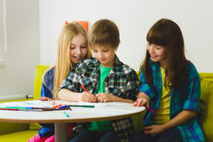 Happy Little girls and boy drawing pictures. Indoor at room Royalty Free Stock Images