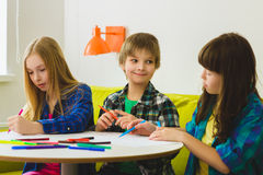 Happy Little girls and boy drawing pictures. Indoor at room Stock Photography