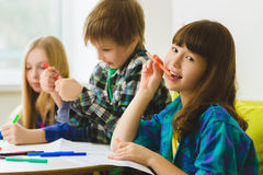 Happy Little girls and boy drawing pictures. Indoor at room. Girl dreaming in front of children.  Stock Photography