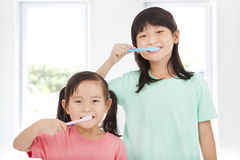 Happy little girls brushing her teeth Stock Photo
