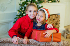 Happy little girls with christmas gift box. Happy little smiling girls with christmas gift box. Christmas interior Stock Photography
