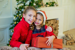 Happy little girls with christmas gift box. Happy little smiling girls with christmas gift box. Christmas interior Royalty Free Stock Photo