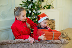 Happy little girls with christmas gift box. Happy little smiling girls with christmas gift box. Christmas interior Stock Image