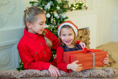 Happy little girls with christmas gift box. Happy little smiling girls with christmas gift box. Christmas interior Stock Images