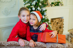 Happy little girls with christmas gift box. Happy little smiling girls with christmas gift box. Christmas interior Royalty Free Stock Image