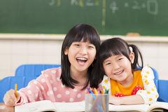 Happy little girls in the classroom Stock Images