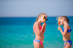 Happy little girls eating ice-cream during beach vacation. People, children, friends and friendship concept Royalty Free Stock Image