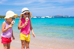 Happy little girls eating ice-cream over summer beach background. People, children, friends and friendship concept Royalty Free Stock Images