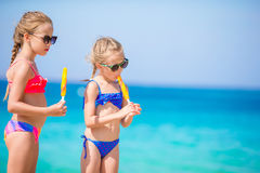Happy little girls eating ice-cream during beach vacation. People, children, friends and friendship concept Stock Image