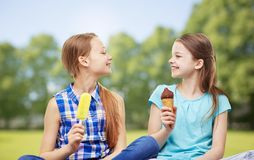 Happy little girls eating ice-cream in summer park royalty free stock image