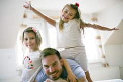 Happy little girls with father at home. royalty free stock image