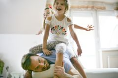 Happy little girls with father at home. stock photo