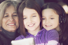 Happy little girls with grandmother with phone Stock Image