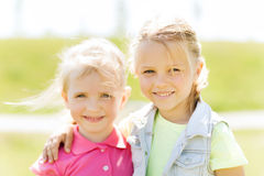 Happy little girls hugging outdoors at summer Royalty Free Stock Photography