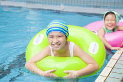 Happy little girls with inflatable ring. Beautiful little girls with inflatable ring at swimming pool stock photography