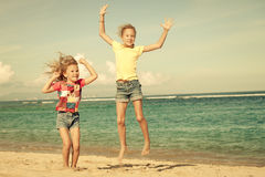 Happy little girls jumping on beach Royalty Free Stock Photos