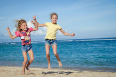 Happy little girls jumping on beach Stock Images