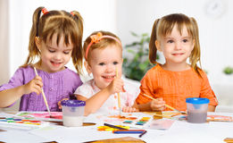 Happy little girls in kindergarten draw paints Royalty Free Stock Photography