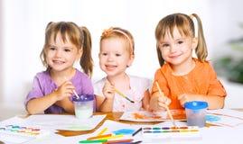Happy little girls in kindergarten draw paints Stock Images