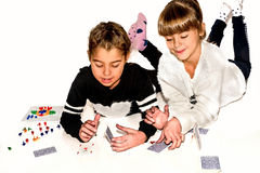 Happy little girls are making house of cards  on white Stock Photos