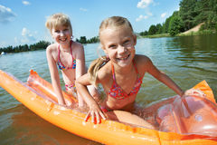 Happy little girls on mattress in lake. At summer Stock Photo