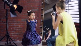 Child photographer holds a photo shoot with a young model. Happy little girls play with the photographer. The model is dressed in Pin up style. A photo session stock video footage