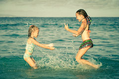 Happy little girls playing at the beach Royalty Free Stock Images