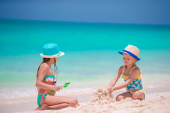 Happy little girls playing on beach sand during tropical vacation Stock Photos