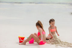 Happy little girls playing on beach sand during tropical vacation. Little girls playing with beach toys during tropical vacation Royalty Free Stock Photo