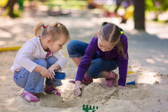 Happy little girls playing in a sendbox Stock Photo