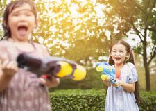 little girls playing water guns in the park stock photography