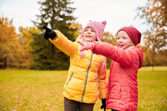 Happy little girls pointing finger in autumn park Royalty Free Stock Image