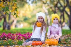 Happy little girls with pumpkins Stock Images