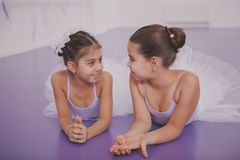 Two little ballerinas talking after dancing lesson royalty free stock image
