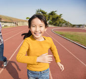 Happy little girls running on the track Stock Images