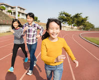 Happy little girls running on the track royalty free stock image